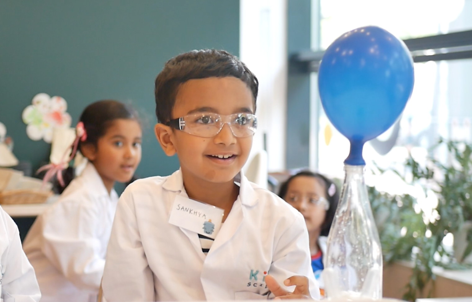 little boy scientist in lab coat watching balloon inflate